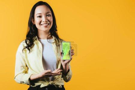 Photo pour Fille asiatique heureuse présentant le smartphone avec la meilleure application d'achats, d'isolement sur le jaune - image libre de droit