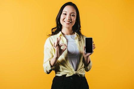Photo pour Attrayant asiatique fille montrant ok signe et smartphone avec écran vide isolé sur jaune - image libre de droit