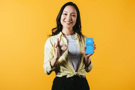 Photo pour Kiev, Ukraine - 16 avril 2019: fille asiatique souriante montrant signe ok et smartphone avec l'application skype, isolé sur le jaune - image libre de droit