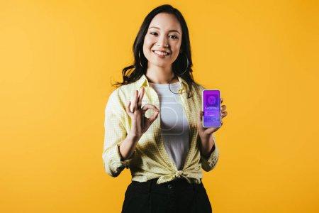 Photo pour Fille asiatique de sourire affichant le signe et le smartphone oks avec l'application d'achats, d'isolement sur le jaune - image libre de droit