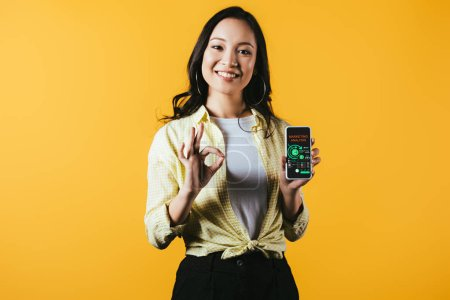Photo for Smiling asian girl showing ok sign and smartphone with marketing analysis, isolated on yellow - Royalty Free Image
