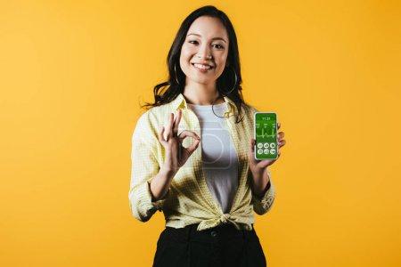 Photo pour Fille asiatique de sourire affichant le signe et le smartphone ok avec l'application de santé, d'isolement sur le jaune - image libre de droit