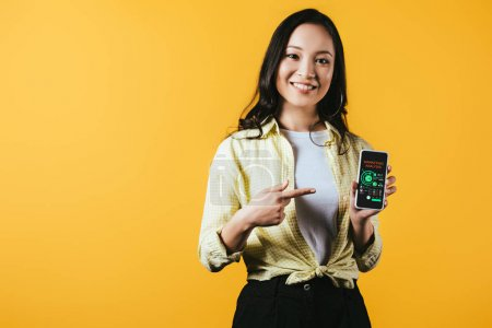 Photo pour Fille asiatique souriante pointant au smartphone avec l'analyse de marketing, d'isolement sur le jaune - image libre de droit