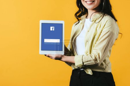 Photo for KYIV, UKRAINE - APRIL 16, 2019: cropped view of smiling girl showing digital tablet with facebook app, isolated on yellow - Royalty Free Image