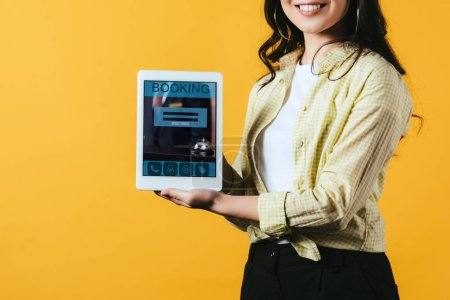 Photo for Cropped view of girl showing digital tablet with booking app, isolated on yellow - Royalty Free Image