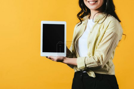 cropped view of girl showing digital tablet with blank screen, isolated on yellow
