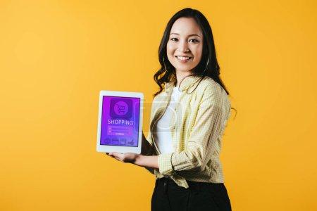 heureux asiatique fille montrant numérique tablette avec shopping app, isolé sur jaune