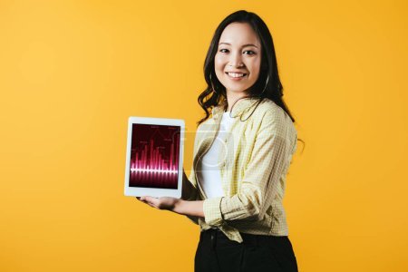 Photo for Happy asian girl showing digital tablet with graph, isolated on yellow - Royalty Free Image