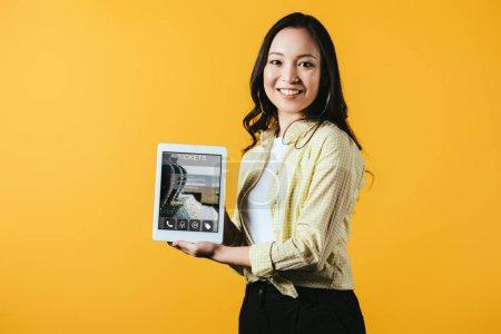 Photo pour Fille asiatique heureuse affichant la tablette numérique avec l'application de billets, d'isolement sur le jaune - image libre de droit