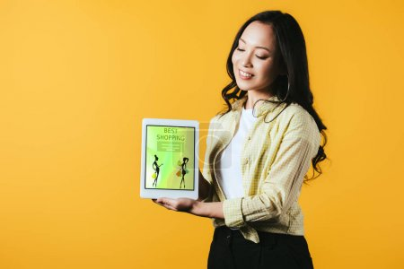 Photo pour Heureux asiatique fille montrant numérique tablette avec meilleur shopping app, isolé sur jaune - image libre de droit