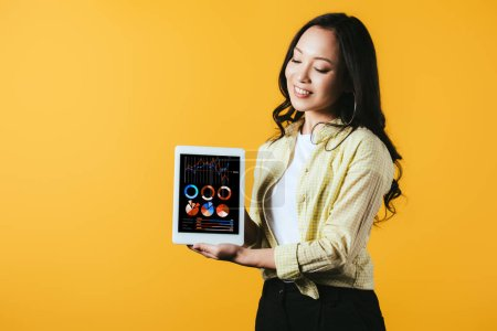 Photo for Happy asian girl showing digital tablet with infographic app, isolated on yellow - Royalty Free Image