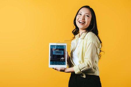 Foto de Chica asiática feliz mostrando tableta digital con aplicación de reserva, aislado en amarillo - Imagen libre de derechos