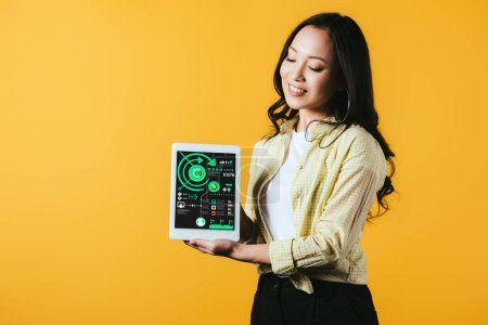 Photo for Smiling asian girl showing digital tablet with infographic, isolated on yellow - Royalty Free Image
