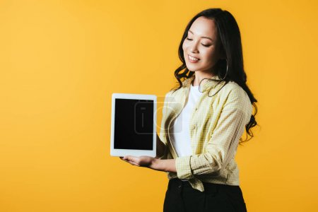 Photo for Young asian woman showing digital tablet with blank screen, isolated on yellow - Royalty Free Image