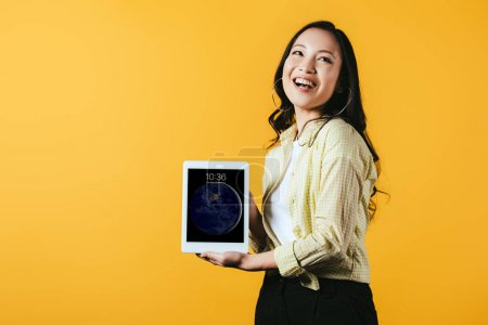 Photo for KYIV, UKRAINE - APRIL 16, 2019: smiling asian girl showing digital tablet screen, isolated on yellow - Royalty Free Image