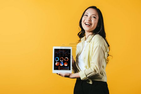 Photo for Smiling asian girl showing digital tablet with infographic app, isolated on yellow - Royalty Free Image