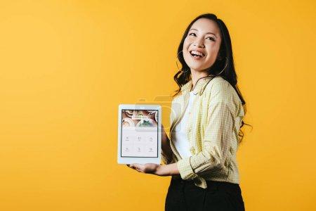 Photo pour KYIV, UKRAINE - 16 AVRIL 2019 : belle fille asiatique montrant tablette numérique avec application quadratique, isolée sur jaune - image libre de droit