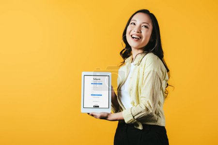 Photo for Smiling asian girl showing digital tablet with instagram app, isolated on yellow - Royalty Free Image