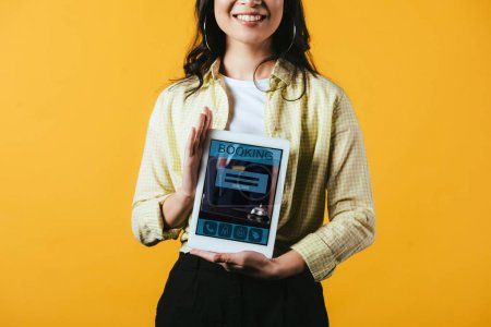Photo for Cropped view of smiling girl showing digital tablet with booking app, isolated on yellow - Royalty Free Image