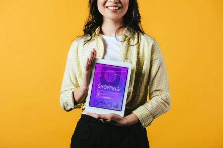 Photo pour Vue recadrée de fille montrant tablette numérique avec application shopping, isolé sur jaune - image libre de droit