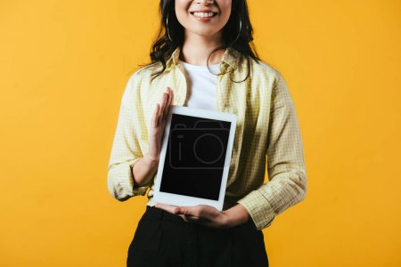 Photo for Cropped view of woman showing digital tablet with blank screen, isolated on yellow - Royalty Free Image