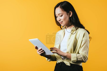 Photo for Young asian woman using digital tablet, isolated on yellow - Royalty Free Image