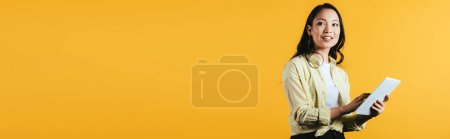 Photo for Smiling asian young woman using digital tablet, isolated on yellow - Royalty Free Image