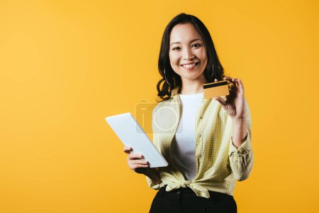 Photo for Smiling asian girl shopping online with digital tablet and credit card, isolated on yellow - Royalty Free Image