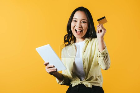 Photo for Happy asian girl shopping online with digital tablet and credit card, isolated on yellow - Royalty Free Image