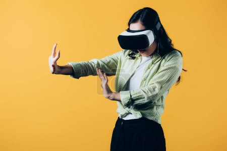 young woman gesturing in Virtual reality headset, isolated on yellow
