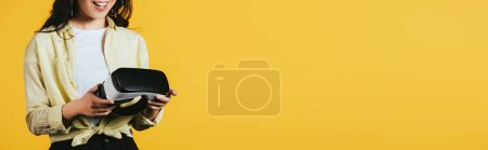 Photo for Cropped view of smiling girl holding Virtual reality headset, isolated on yellow - Royalty Free Image