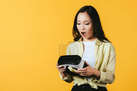 Photo for Cropped view of surprised asian girl holding Virtual reality headset, isolated on yellow - Royalty Free Image