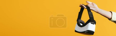 Photo for Partial view of woman holding Virtual reality headset, isolated on yellow - Royalty Free Image