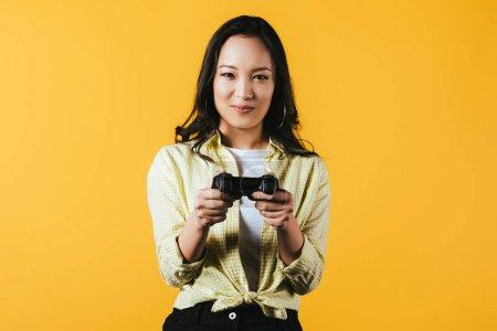 Photo pour Kiev, Ukraine - 16 avril 2019: femme asiatique souriante jouant au jeu vidéo avec joystick, isolée sur le jaune - image libre de droit