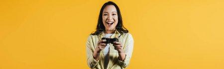 Photo pour Kiev, Ukraine - 16 avril 2019: femme asiatique heureuse jouant au jeu vidéo avec joystick, isolée sur le jaune - image libre de droit