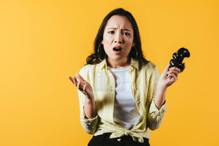 Photo for KYIV, UKRAINE - APRIL 16, 2019: upset asian girl playing video game with joystick, isolated on yellow - Royalty Free Image