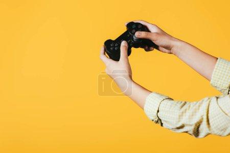 Foto de Kiev, Ucrania - 16 de abril de 2019: vista recortada de la mujer jugando videojuego con joystick, aislada en amarillo - Imagen libre de derechos