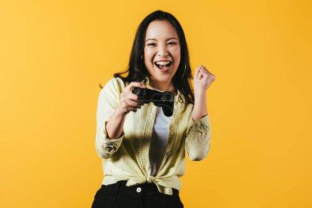 Photo pour Kiev, Ukraine - 16 avril 2019: fille asiatique heureuse jouant au jeu vidéo avec joystick, isolée sur le jaune - image libre de droit