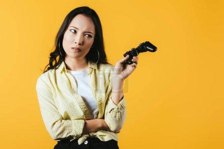 Photo pour Kiev, Ukraine - 16 avril 2019: jolie fille asiatique tenant joystick, isolée sur le jaune - image libre de droit