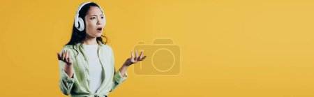 Photo pour Attrayant frustré asiatique femme écoute de la musique avec casque, isolé sur jaune - image libre de droit