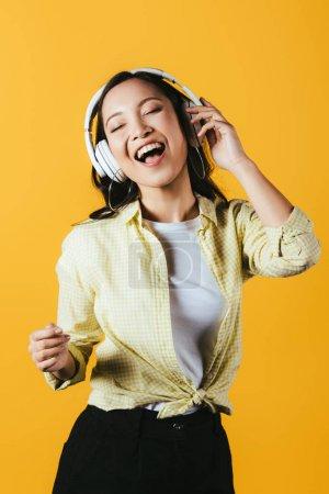 Photo pour Joyeuse asiatique femme chant et écouter de la musique avec casque, isolé sur jaune - image libre de droit