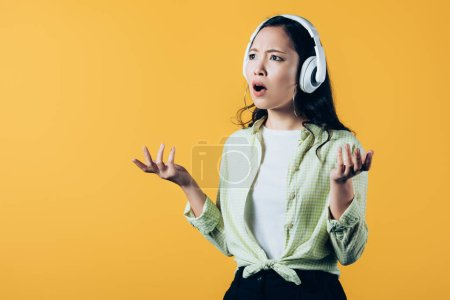frustrated asian girl listening music with headphones, isolated on yellow