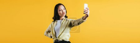 Photo for Brunette asian woman taking selfie on smartphone isolated on yellow - Royalty Free Image