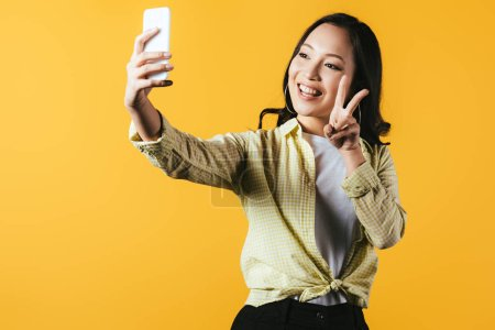 Photo pour Attractive asian girl showing peace symbol and taking selfie on smartphone isolated on yellow - image libre de droit
