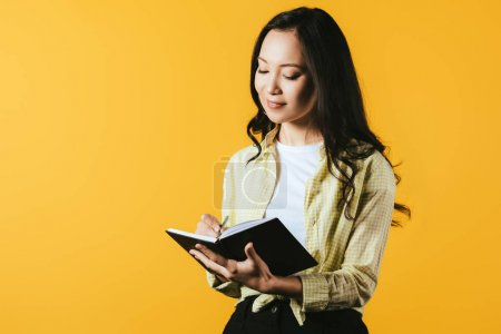 Photo for Smiling girl writing in notebook with pen, isolated on yellow - Royalty Free Image