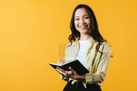 Photo pour Heureux asiatique fille écriture dans notebook avec stylo, isolé sur jaune - image libre de droit