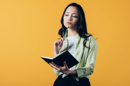 Photo for Pensive asian girl with notebook and pen, isolated on yellow - Royalty Free Image