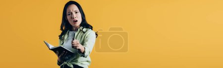 Photo pour En colère asiatique étudiant avec notebook et stylo, isolé sur jaune - image libre de droit