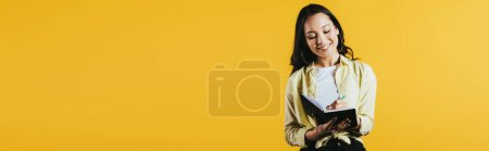 Photo for Smiling asian girl writing in notebook with pen, isolated on yellow - Royalty Free Image