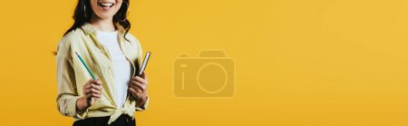 Photo for Cropped view of girl with notebook and pen, isolated on yellow - Royalty Free Image